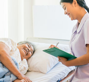 Nurse filling out a chart next woman in hospital bed