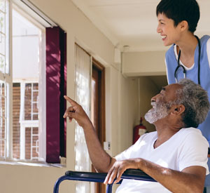 Man in wheel chair point showing a nurse something out the window