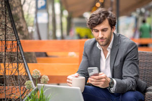 Man working on phone and laptop